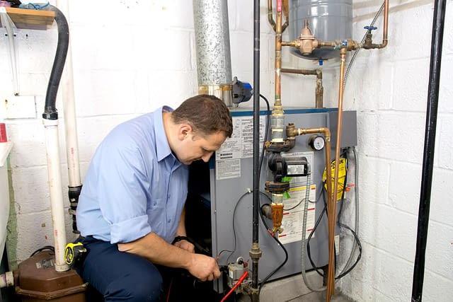 Hvac technicians working indoors on a boiler unit