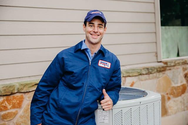 HVAC technician next to an outdoor ac unit