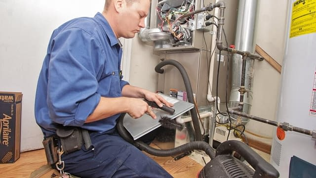 HVAC technician cleaning and repair an indoor heating system