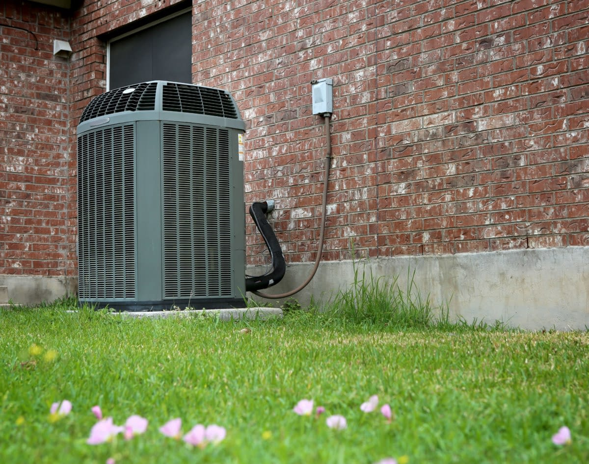 Modern AC heating unit attached to a brick wall