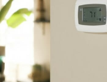 Air conditioning thermostat mounted on wall displaying seventy one degrees