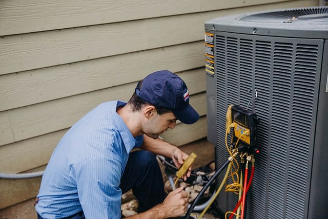 hvac technician inspecting outdoor unit