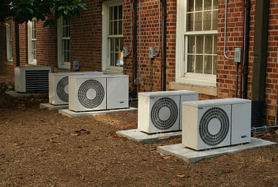 Five air conditioning units outside of red brick building